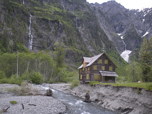 Olympic National Park's Enchanted Valley Chalet is expected to be temporarily moved in September. Recent photos show the shifting East Fork Quinault River is undercutting the chalet by about eight feet.