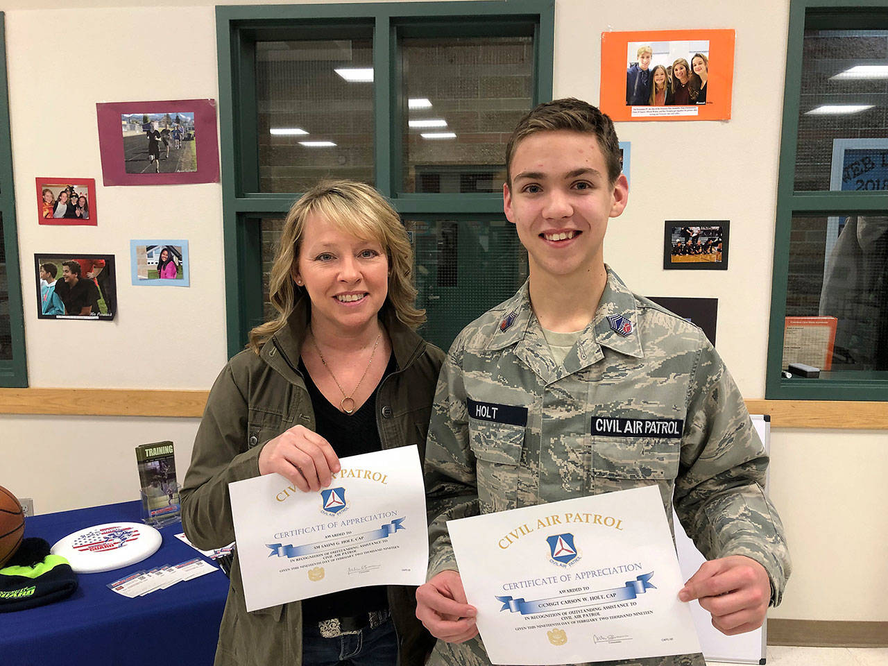 Two Civil Air Patrol members, senior member Sauni Holt and cadet CMSgt. Carson Holt, show certificates they received with challenge coins for their recent donation to the organization's unit in Sequim. Photo courtesy of Civil Air Patrol                                 Two Civil Air Patrol members, senior member Sauni Holt and cadet CMSgt. Carson Holt, show certificates they received with challenge coins for their recent donation to the organization's unit in Sequim. Photo courtesy of Civil Air Patrol
